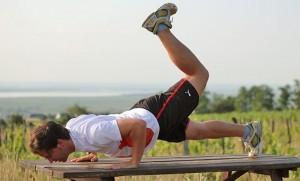 Skorpion Liegestütze richtig machen: Ein Bein während des Armbeugens abwinkeln und anheben, bei der nächsten Wiederholung das andere Bein.