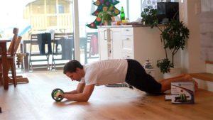 Beim Bauchrollen mit Trizepsdrücken berühren deine Ellenbogen kurz den Boden.
