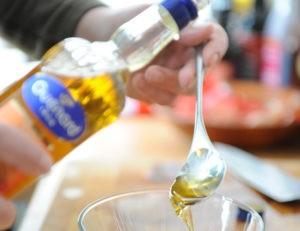 Glasflasche, Löffel, Walnussöl, Schüssel, Hand